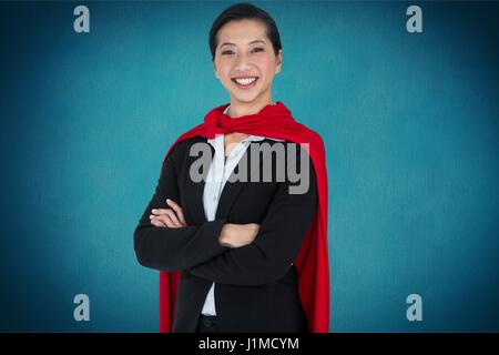 Digital composite of Portrait of businesswoman wearing cape while standing against blue background - Stock Photo
