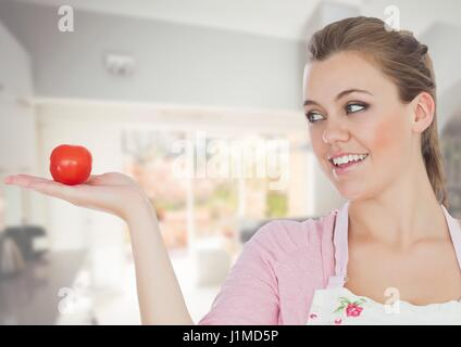 Digital composite of Cook woman in the kitchen of the house looking the tomato - Stock Photo