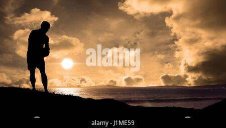 Digital composite of Silhouette sportsman at beach during sunset