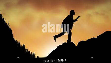 Digital composite of Silhouette businessman walking on mountain during sunset - Stock Photo