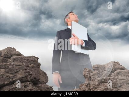 Digital composite of Business man with laptop and flare looking up behind rocks - Stock Photo