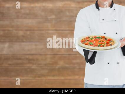 Digital composite of Chef showing the pizza. Blurred wood background - Stock Photo