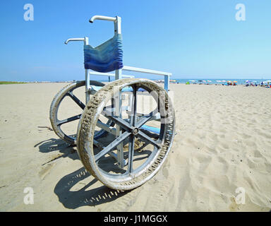 ... Special wheelchair with big steel wheels to go on the sand - Stock Photo