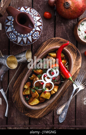 Ojaxuri, roasted pork and potatoes with onion and pomegranate seeds. Top view - Stock Photo