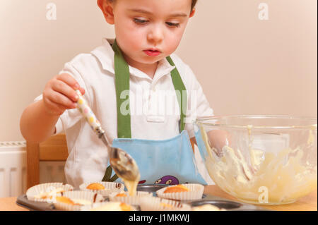 Young boy baking cupcakes in his kitchen - Stock Photo