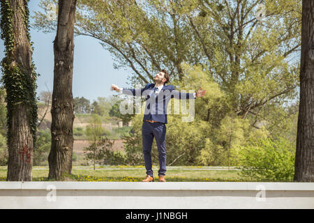 young man, looking up above, standing on wall, arms outstreched, sunny day outdoors nature, formal clothes suit - Stock Photo