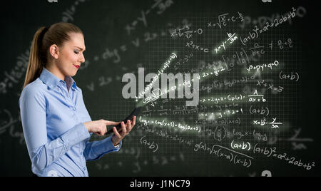 Young woman using calculator over design background - Stock Photo