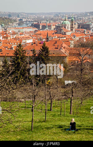 Woman admiring the view over the roof tops of Prague towards the Vltava river and its bridges - Stock Photo