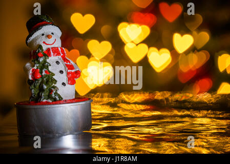 Christmas snowman and heart shaped lights in background, heart shaped bokeh blur - Stock Photo