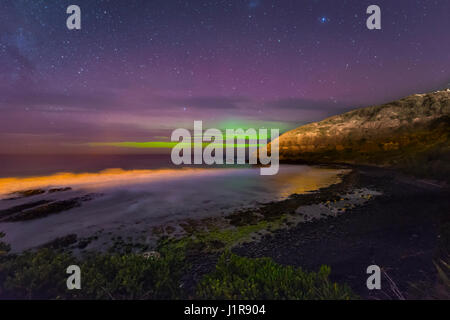 Southern lights, aurora australis over the sea, sand dunes, Second Beach, Dunedin, Otago, Southland, New Zealand - Stock Photo