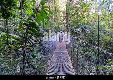 Woman walking over suspension bridge, Rainforest, Mistico Arenal suspension bridges Park, Volcan Arenal National - Stock Photo