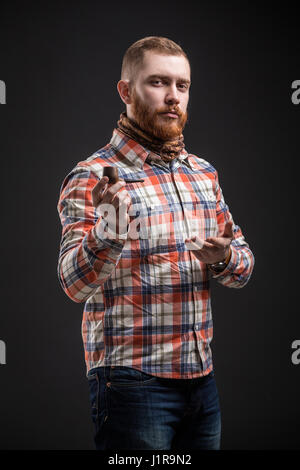 Portrait of handsome bearded man in checked shirt presenting smoking pipe, Studio shot, Isolated - Stock Photo