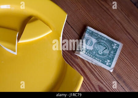 Broken yellow plate and one dollar on wooden background as a symbol of the crisis. - Stock Photo