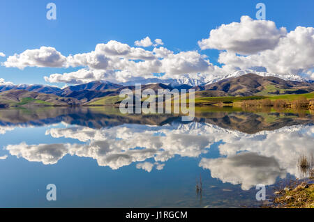 Reflection of the snowy mountains in a lake near Fairlie in the Southern Island, New Zealand - Stock Photo