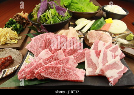 Fresh sliced beef with vegetables on tables in the kitchen - Stock Photo