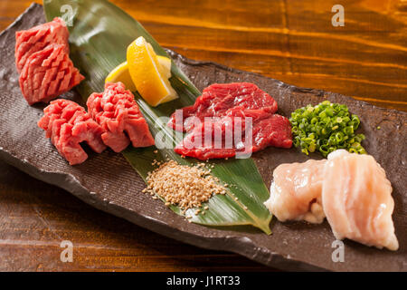 Fresh raw red beef with lemon on stone cutting board - Stock Photo