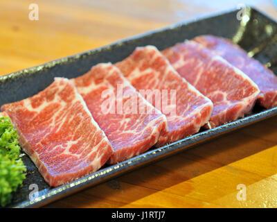 Fresh raw sliced beef on black platter - Stock Photo