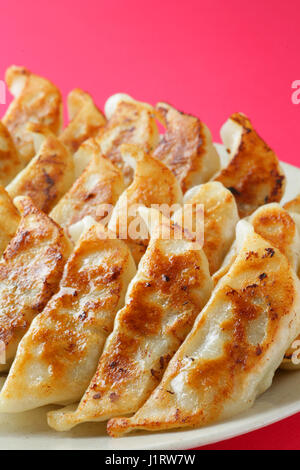 Japanese dumplings on white dish - Stock Photo