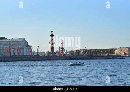 Pleasure boat floats on the Neva river on the background of the Rostral columns in Saint-Petersburg  in May - Stock Photo