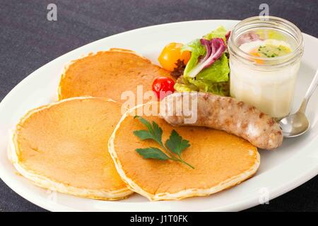 Fried sausages with  lettuce, bread and juicy fruit on white platter - Stock Photo