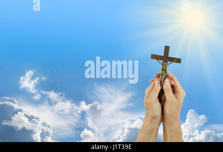 Praise to Our Lord - Female hands gently holding a Crucifix of Jesus Christ up towards a shining sun in a blue sky - Stock Photo