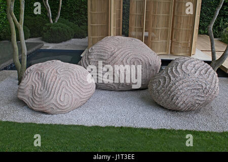 Sculpture showing the intervention of humans into nature in a garden setting - Stock Photo