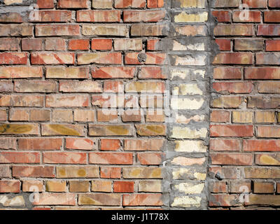 On an old wall of red bricks a separated vertical fragment of the old silicate brick - Stock Photo