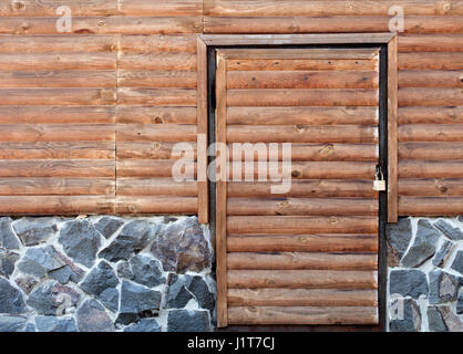 Wooden door to the back room of the log house and a stone foundation - Stock Photo