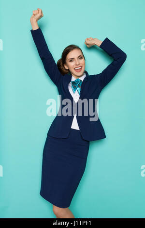 Happy young woman in blue suit and turquoise scarf is standing with arms outstretched and laughing. Three quarter - Stock Photo