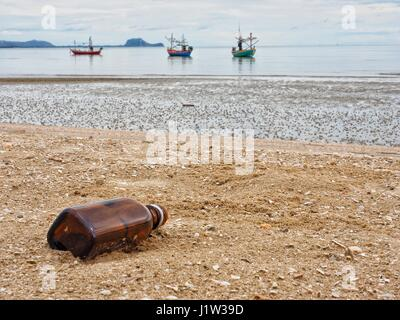 A brown glass bottle thrown away in the beautiful sand beach as garbage, waste on sand, polluted sea, Dolphin Bay, - Stock Photo