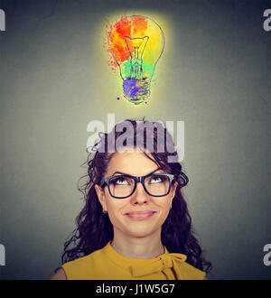 Portrait of a woman with glasses and creative idea looking up at colorful light bulb on gray wall background. Inspiration - Stock Photo