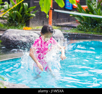 Asian Girl Jump into Swimming Pool - Stock Photo
