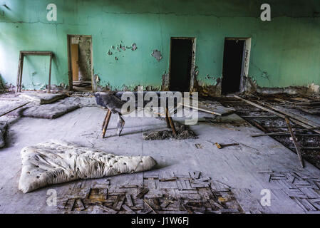 Gymnastic horse in High school No 2 in Pripyat ghost city of Chernobyl Nuclear Power Plant Zone of Alienation in - Stock Photo