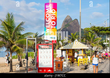 RIO DE JANEIRO - FEBRUARY 21, 2017: Colorful Welcome to Rio sign stands above Ipanema Beach as locals pass on the - Stock Photo