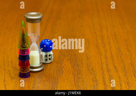 Six colored pawns and two dice isolated on a wooden background macro - Stock Photo