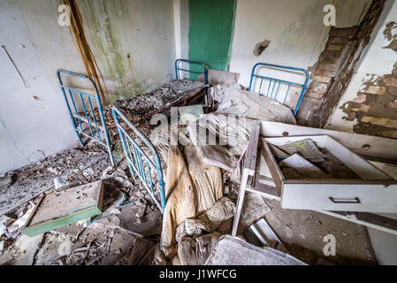 Room in old secondary school in Mashevo abandoned village of Chernobyl Nuclear Power Plant Zone of Alienation in - Stock Photo
