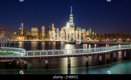 New York City Financial District skyscrapers and Hudson River from Hoboken promenade in evening. Lower Manhattan - Stock Photo