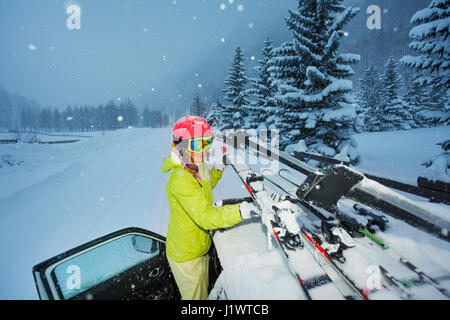 Portrait of young woman fastening skis on the car roof after ski trip in the evening - Stock Photo