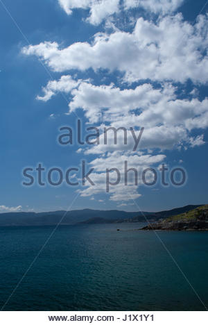 Rock waterfront seacscape & mountains across water - Stock Photo