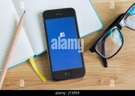 Bangkok, Thailand - April 22, 2017 : Apple iPhone5s showing its screen with Facebook application. - Stock Photo