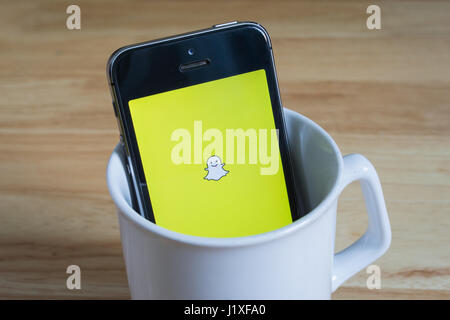 Bangkok, Thailand - April 22, 2017 : Apple iPhone5s in a mug showing its screen with Snapchat logo. - Stock Photo
