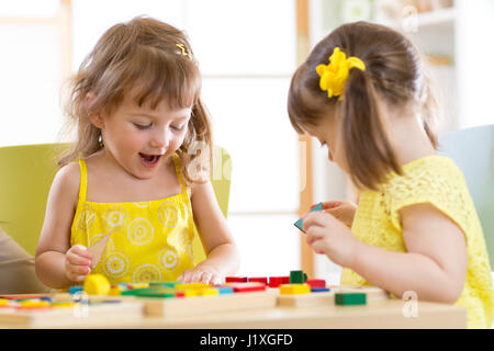 Kids playing with colorful block toys. Two children girls at home or daycare center. Educational child toys for - Stock Photo