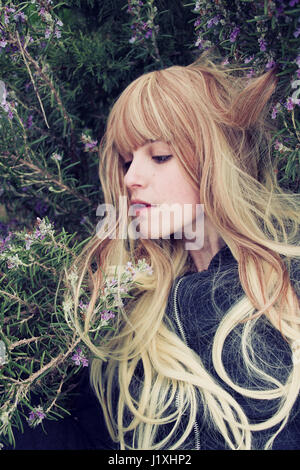 Young woman lying in a rosemary bush - Stock Photo