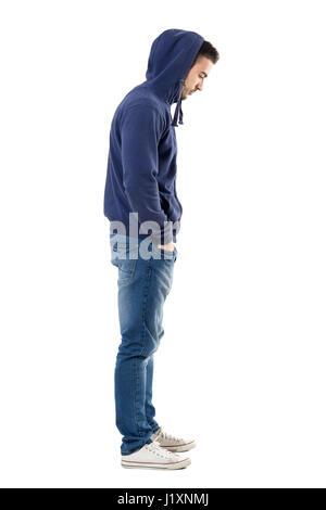 Side view of sad upset man in hooded shirt with hands in pockets looking down. Full body length portrait isolated - Stock Photo