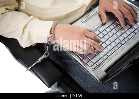 A shot of a businessman handcuffed on a chair working on his laptop - Stock Photo