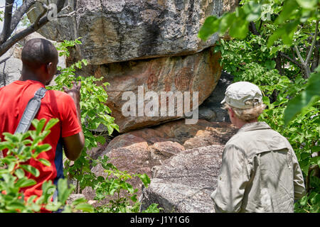 tourist and guide looking on Rock art, ancient San paintings, Tsodilo Hills, Botswana, Africa - Stock Photo