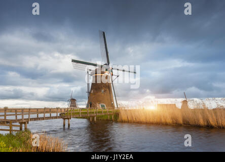 Amazing windmills at sunset. Rustic landscape with traditional dutch windmills, bridge near the water canals and - Stock Photo