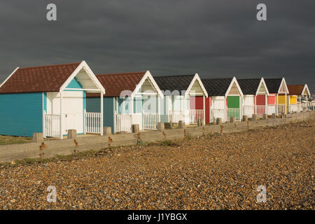 Colourful beach huts on the seafront at Lancing, West Sussex, England. With very dark and stormy sky - Stock Photo