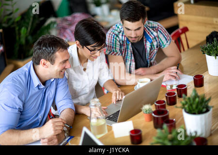 Three business people working on laptop shop in coffee - Stock Photo