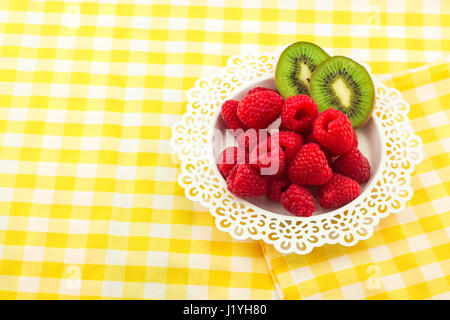 Fresh Red Raspberries on a white artistic plate / Red Fresh Raspberries on a white artistic plate with cookies, - Stock Photo